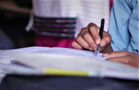 This image shows a young person's hand writing