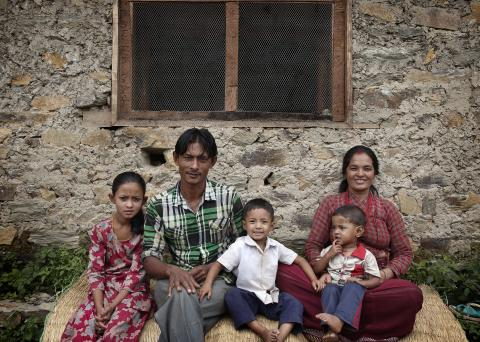 This image shows a family - a father, mother and three children in front o their home