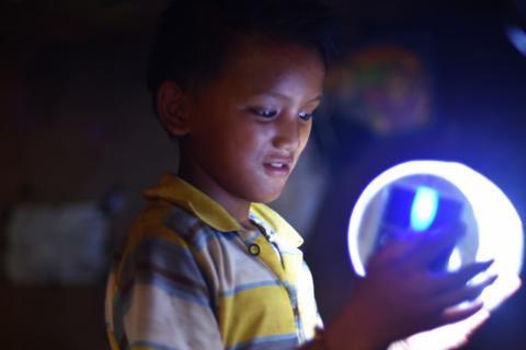 This image shows a young boy from Lekhnath, Kaski, holding a solar powered lamp in his hands