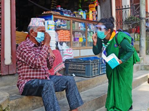 This image shows a nepal scout teaching an elderly man to wear a mask properly