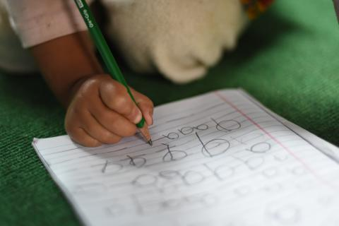 This image shows a child practicing writing on a notebook