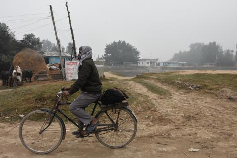 This image shows a scene from the Chamar village in Mithila Municipality in Dhanusha District, with a man passing by on his bicycle