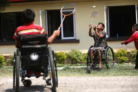 Young children playing Badminton with the help of Wheel Chair