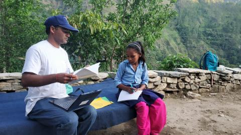 This image shows MICS enumerator Mahesh Bikram Bohara conducting a survey with girl child Mamita Pari in Bajura District in Nepal's far-west