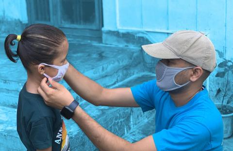 This image shows a UNICEF staff member putting a mask on his child