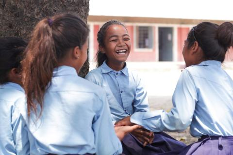 Rejina Nepali (centre) laughing with her friends in her school in Tulsipur, Dang District.
