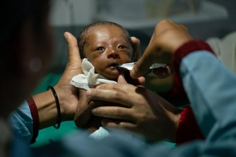 A nurse at the Seti Zonal Hospital helps Sabina to feed her baby some milk using a nifty cup.