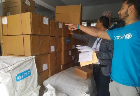 This image showsUNICEF staff and provincial health officials in Sudur Paschim province examining supplies provided by UNICEF as part of the COVID-19 response. The supplies include surgical masks, gloves, hand sanitizers, along with blankets and bed nets for people staying in quarantine, and tents to establish a fever clinic in the provincial hospital, among other materials.