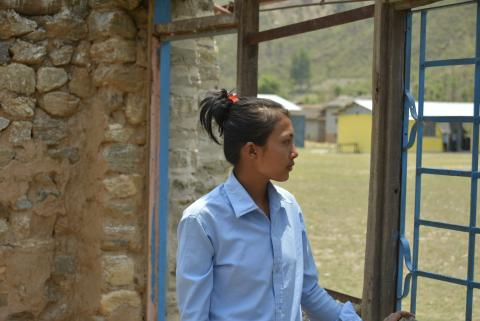 Indira Shrestha looks at the ruins of her school damaged by the earthquake. The new Transitional Learning Centre built through EU-UNICEF project Restoring Education can be seen from the window