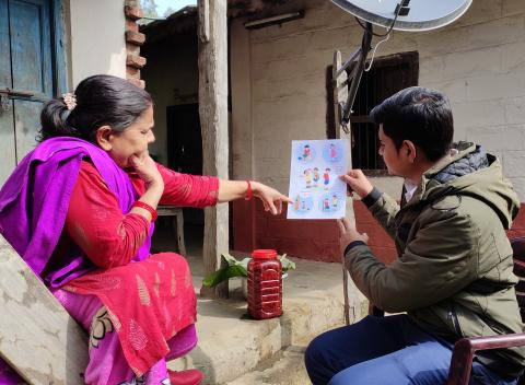Mental health coordinator at the Mithila Municipality in Dhanusha District, Nirmal Mahato (right) and female community health volunteer Sarita Dahal (left) pore over a flyer detailing different mental health disorders among children and adolescents.