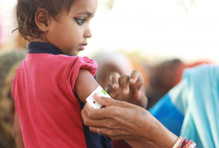 This image shows a young child getting her upper arm measured by a female community health volunteer in Dhanusha District