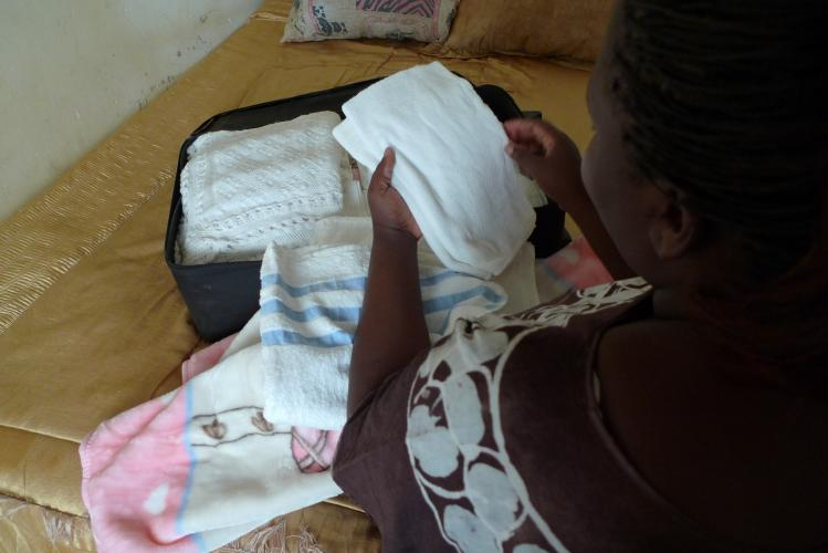 This image shows a woman unpacking baby clothes and blankets in her home in Lusaka. She has just returned following the stillbirth of her baby. She believes her baby was stillborn due to complications related to her diabetes and HIV-positive status.
