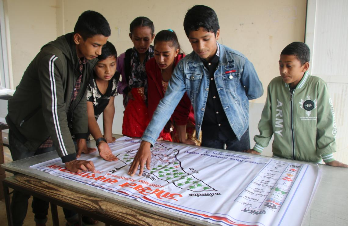 Members of the Nectar Child Club in Dolakha District around a hazard map that they helped develop