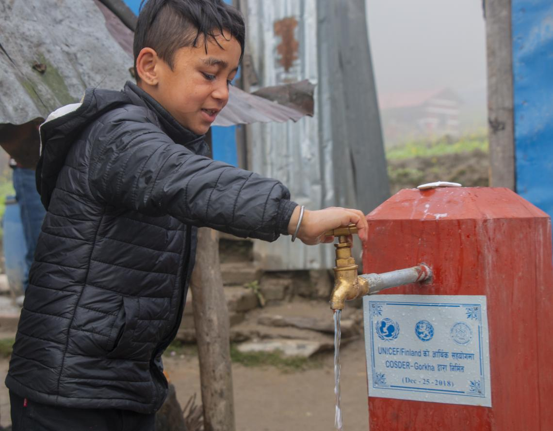 Boy using water tap