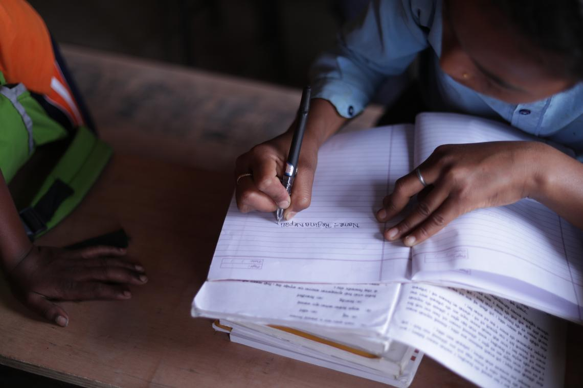 Rejina Nepali writes in her notebook in her school in Tulsipur, Dang District.