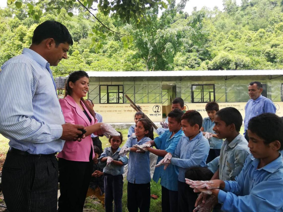 Sushmita (second from left) demonstrating proper handwashing technique to schoolchildren in Gorkha District.