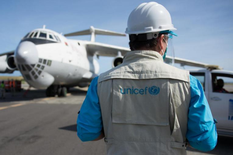 This image shows a UNICEF staff on an airport runway.