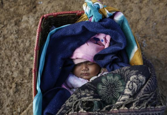 This image shows a child sleeping in a cot