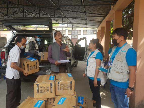 This image shows UNICEF staff handing over supplies to health officials in Sudur Paschim as part of the COVID-19 response. The supplies include surgical masks, gloves, hand sanitizers, along with blankets and bed nets for people staying in quarantine, and tents to establish a fever clinic in the provincial hospital, among other materials.