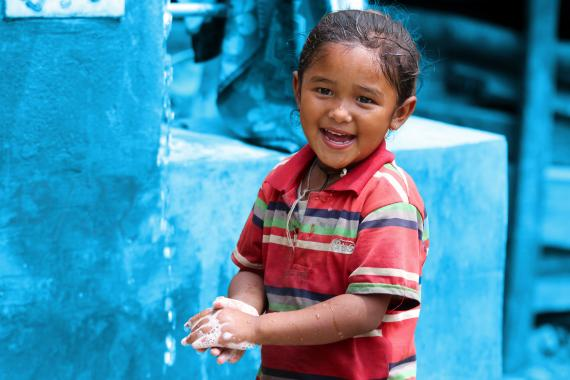 This image shows a child washing hands with soap and smiling