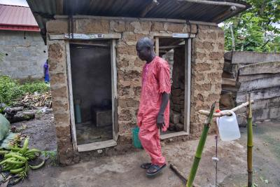 A man stands in front of a latrine