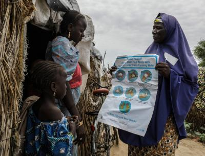 A volunteer community mobilizer teaching about hygiene in a camp in Borno