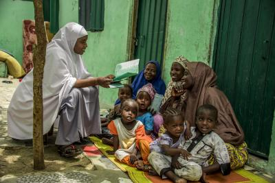A health worker teaching mothers about immunization
