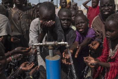 Children drinking clean water from a tap.