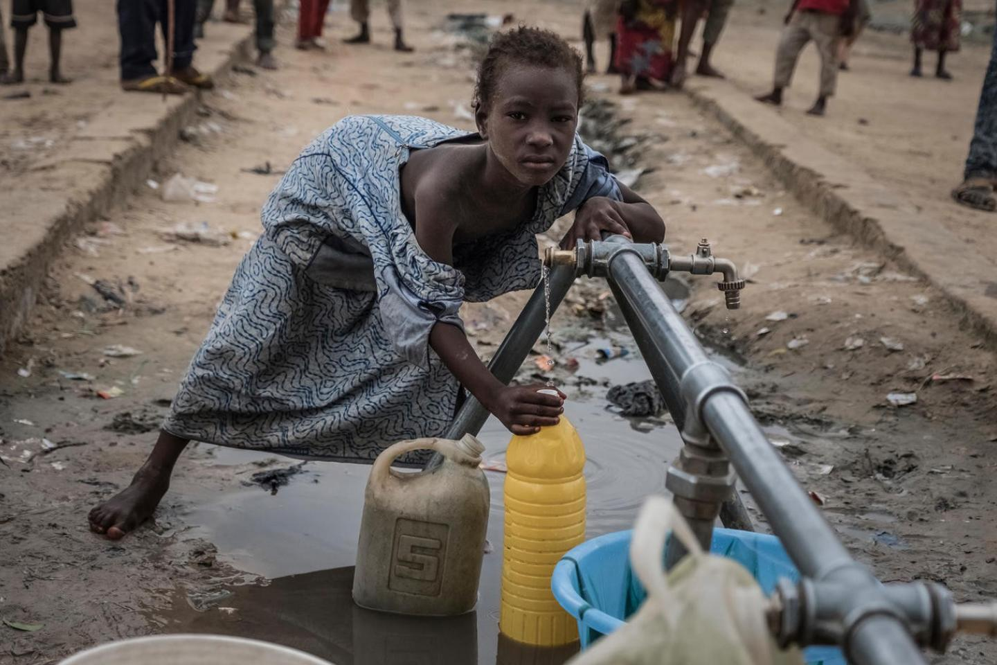 Girl-filling-water-container-in-camp