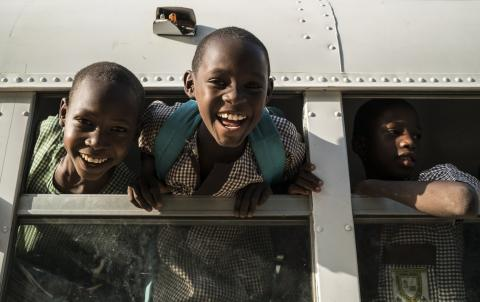 Schoolchildren peek out through a school bus window