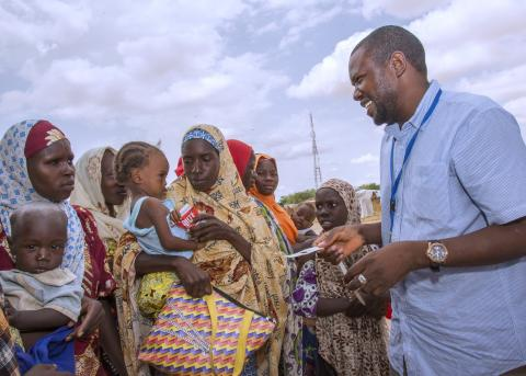 A UNICEF staff gives a mother therapeutic food for her baby