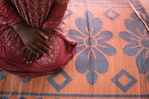 A girl kneeling on a mat