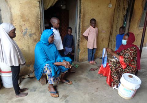 A volunteer hygiene promoter talking to a family