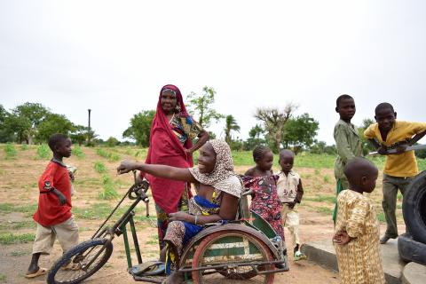 A woman in a wheelchair surrounded by children in her community