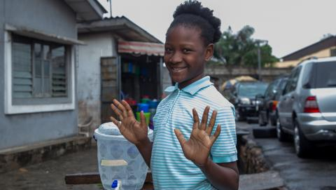 A girl shows her clean hands after handwashing