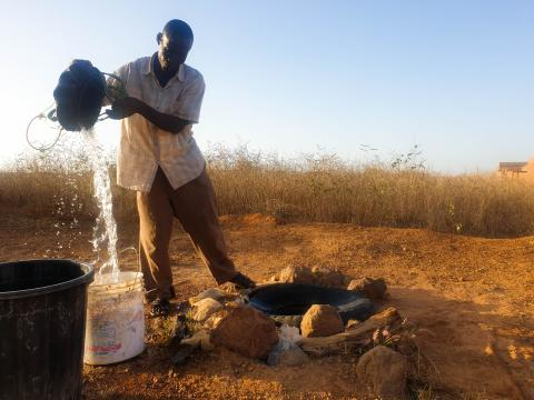 Health worker fetching water from a well