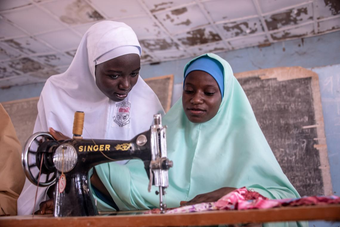 Girls using a sewing machine