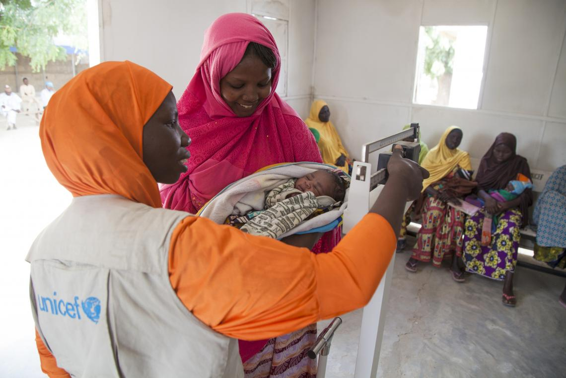 A new born baby and her mother are weighed in a UNICEF-supported health clinic in Muna Garage IDP camp, Maiduguri, Borno State.