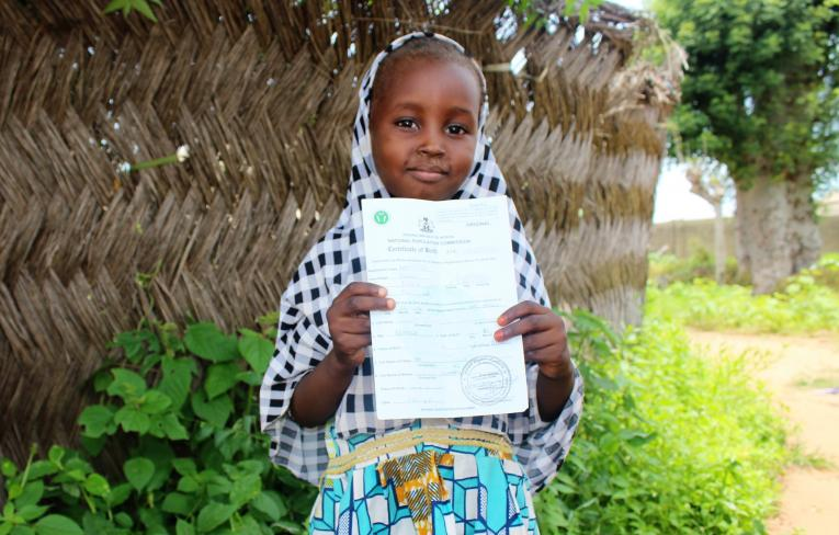 A girl stands with her birth certificate