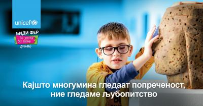 A billboard depicting a child with visual impairment exploring a statue with his fingers and arms, with the message - Where some see a disability, we see a curiosity