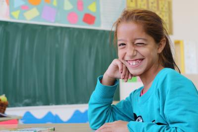 A girl in a schoolroom winking and smiling