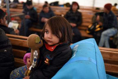 A child with a doll sitting at a refugee and migrant transit centre in Tabanovce