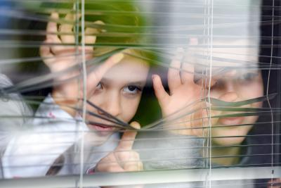 A small girl and her bigger brother are looking through Venetian blinds