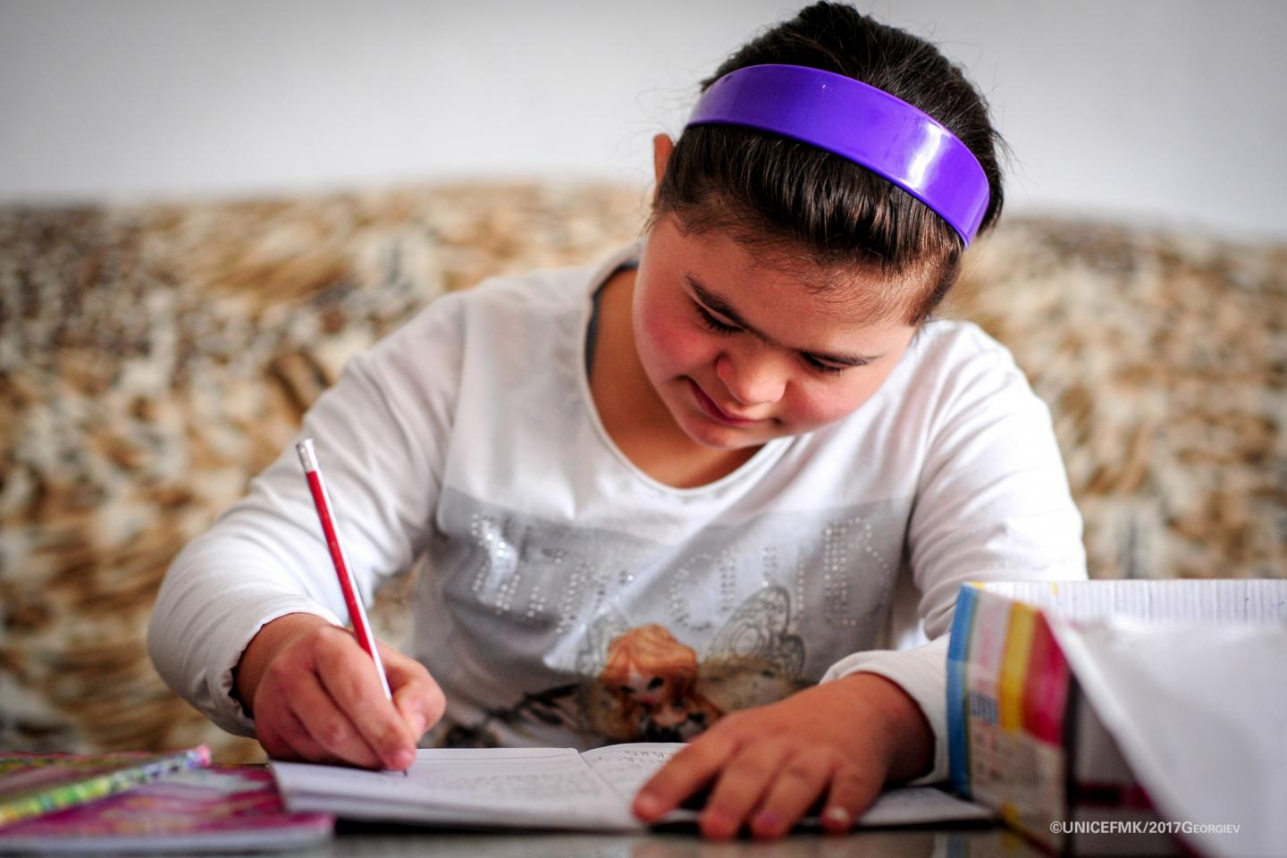 12 year old Stefanija who has down syndrome writes down in her notebook in the living room of her family house in Delcevo