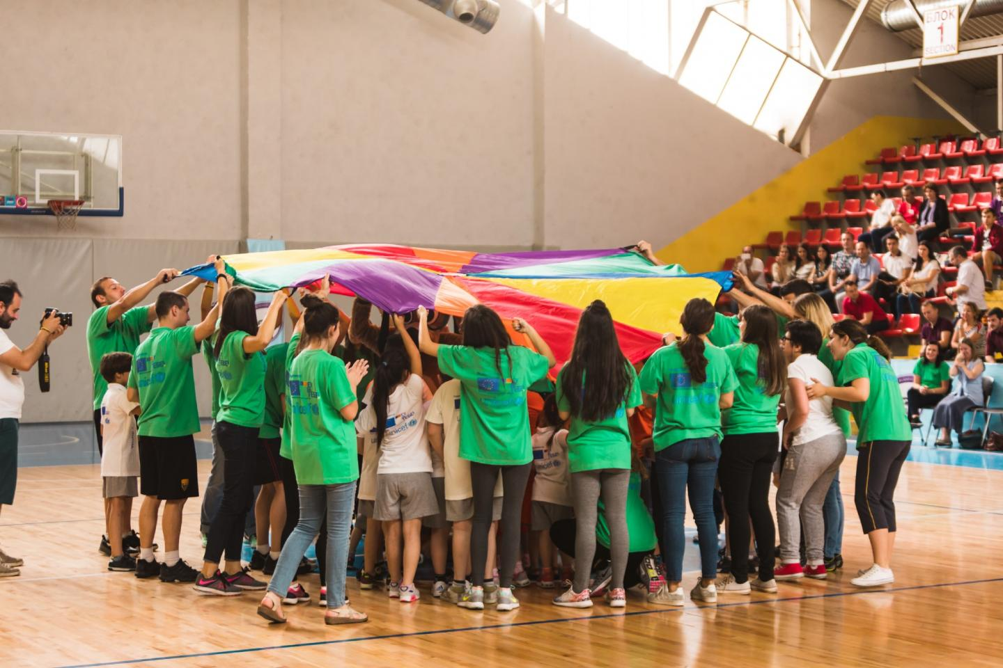 A group of children celebrate under a giant multi-coloured flag after a sport events