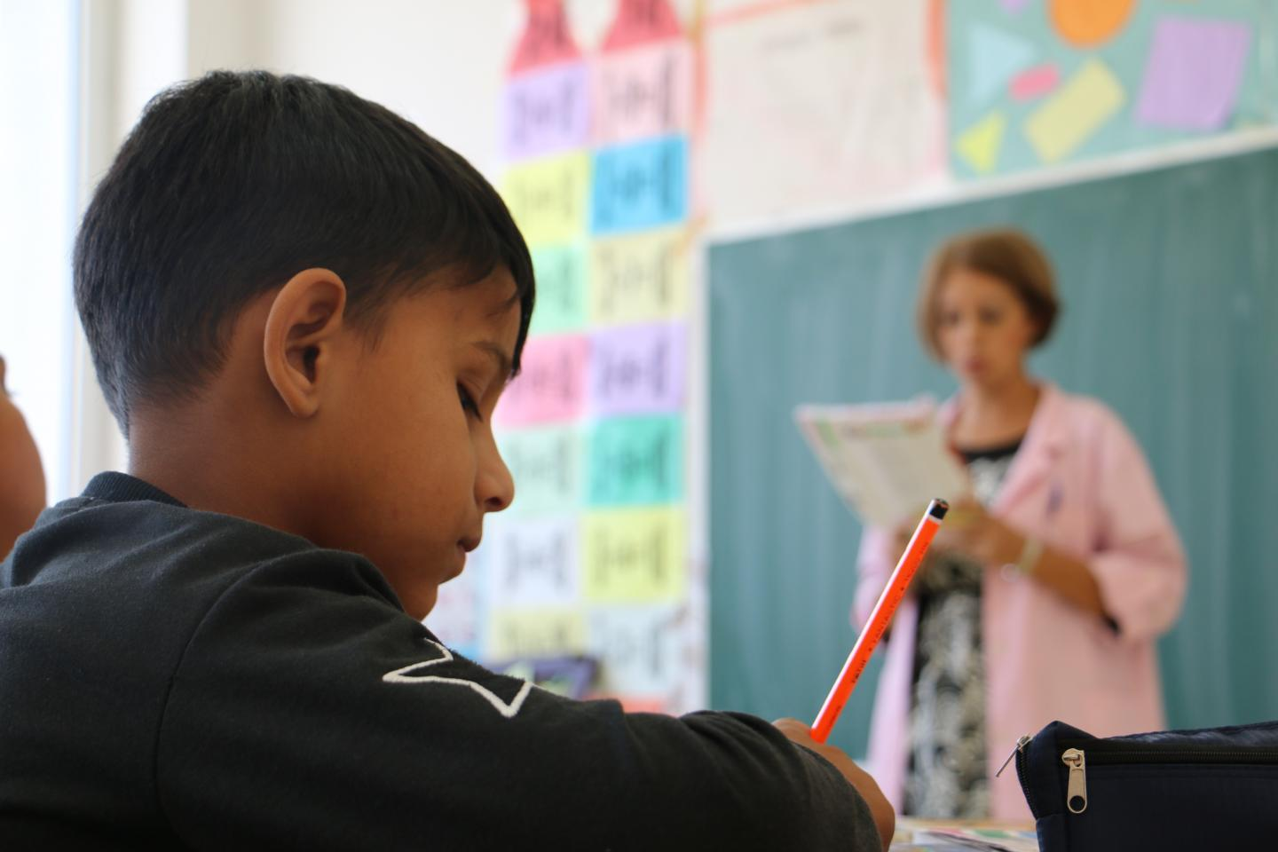 a child writing down notes from the teacher's lesson as she speaks in a classroom