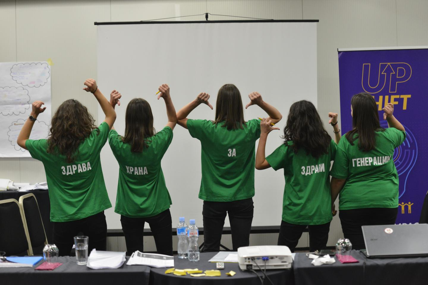 The team of five girls wearing green shirts each of which contains a single word, jointly creating the message - healthy food for healthy generations
