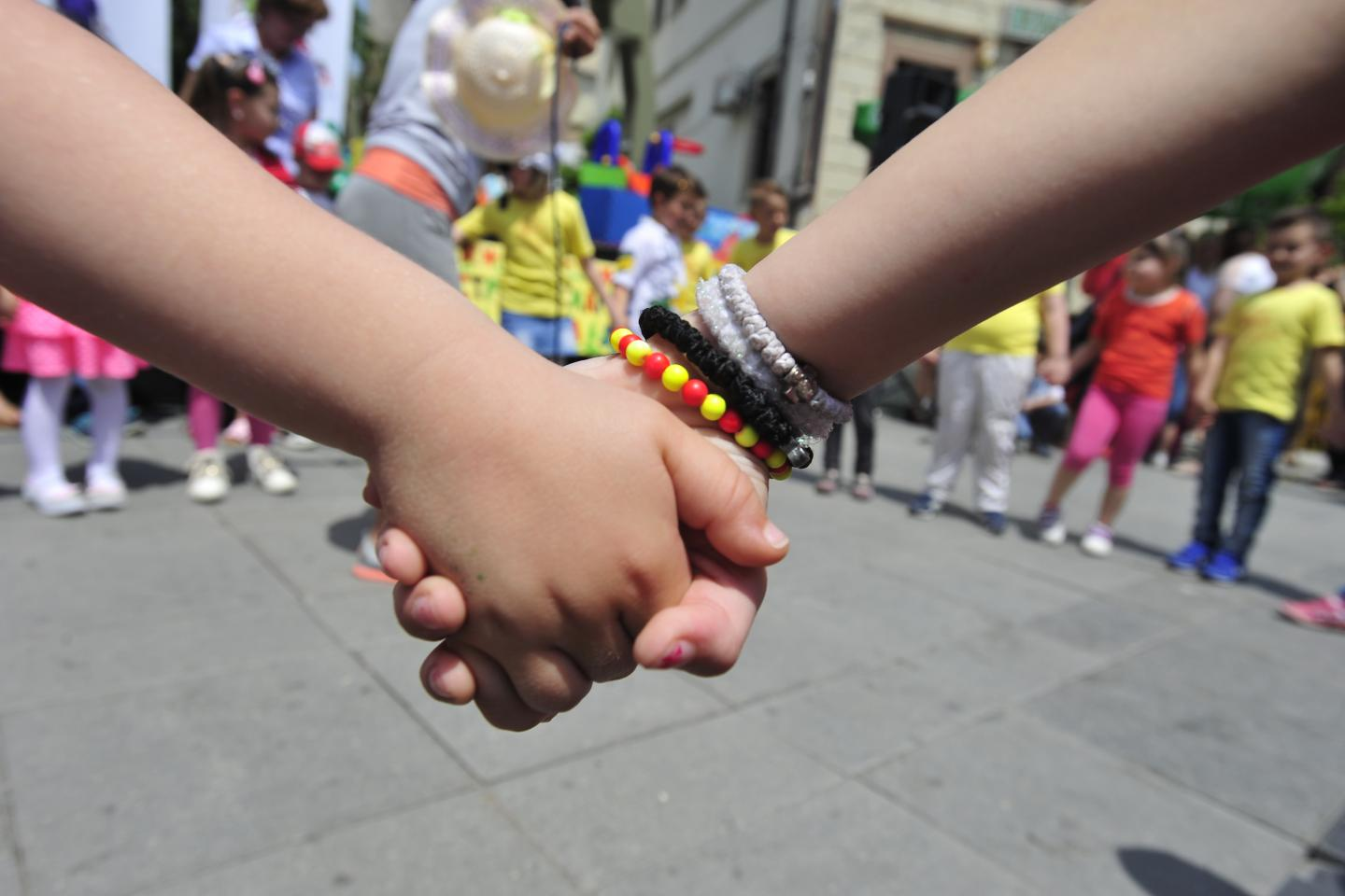 Close up image of the hands of two children holding each other's hand