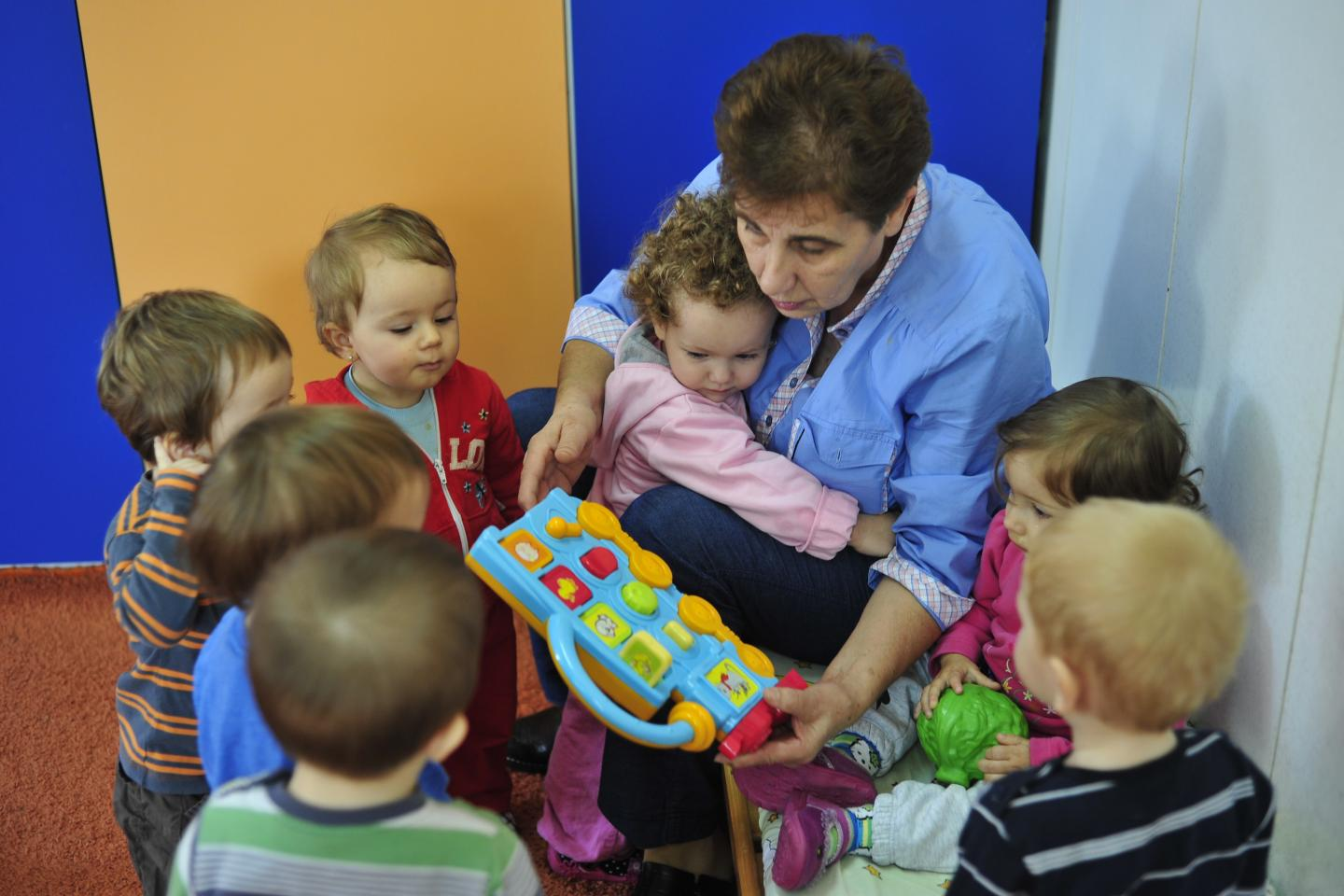 a kindergarten teacher with a lot of children surrounding her, explaining how a learning toy functions