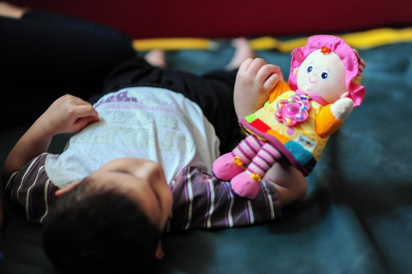 A child laying on the floor is looking at a doll that he holds in his right hand